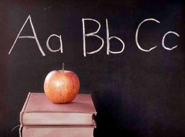 Apple on top of books with alphabet on chalkboard in background.
