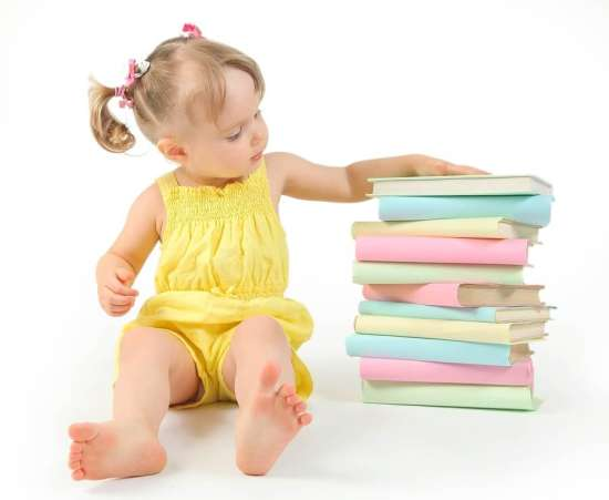 Little girl sitting next to stack of books