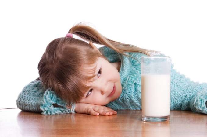 Little girl sitting at table with glass of milk