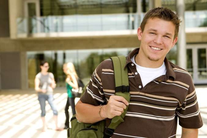 Male student standing in front of school with backpack