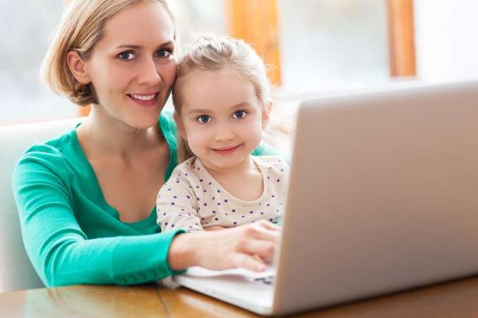Mother and daughter sitting at desk using laptop