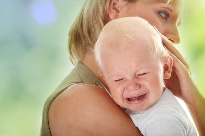 Stressed mom holding crying baby