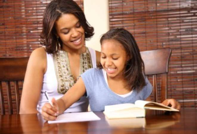 Mother helping daughter do homework.