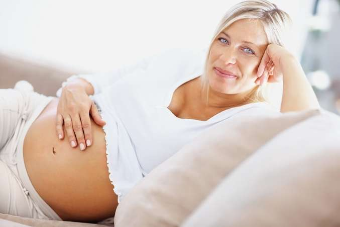 Smiling pregnant woman sitting in chair