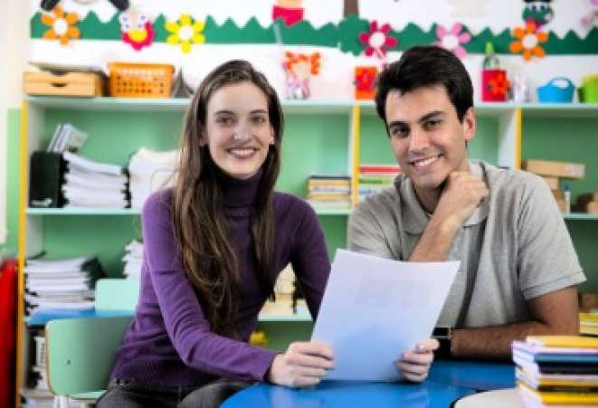 Parent and teacher sitting in classroom talking