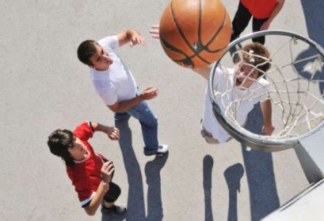 Groupd of teens playing a game of outdoor basketball