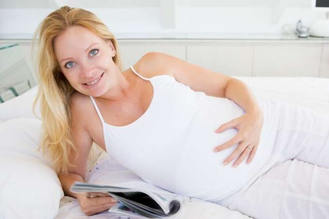 Pregnant woman reading in bed