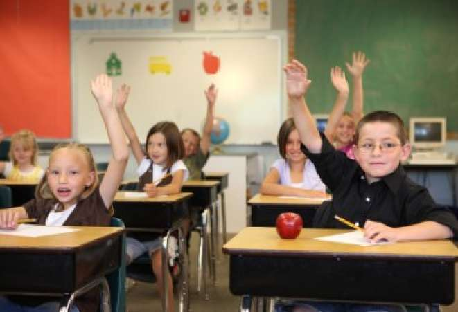 Eager students raising hands in classroom.