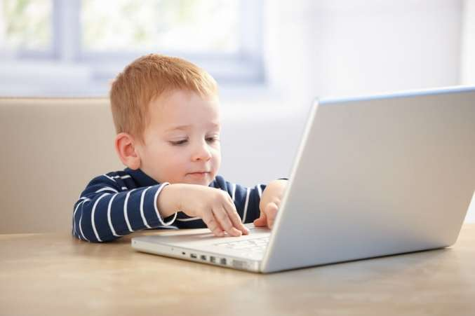 Young redheaded boy using laptop
