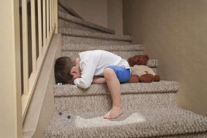 Crying boy laying on stairs