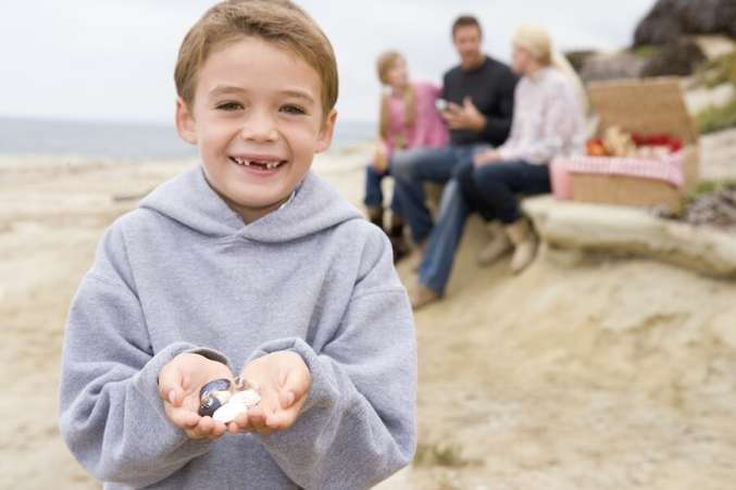 Boy holding a pile of seashells in hand