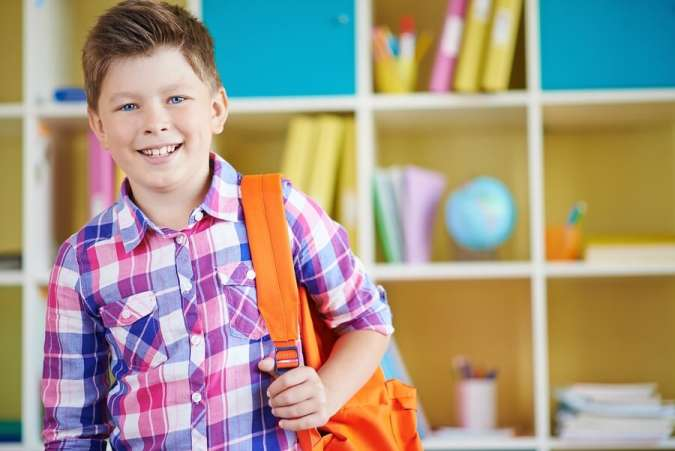 Smiling boy with backpack standing in mudroom