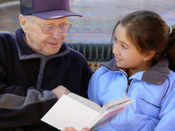 Grandfather reading to granddaughter