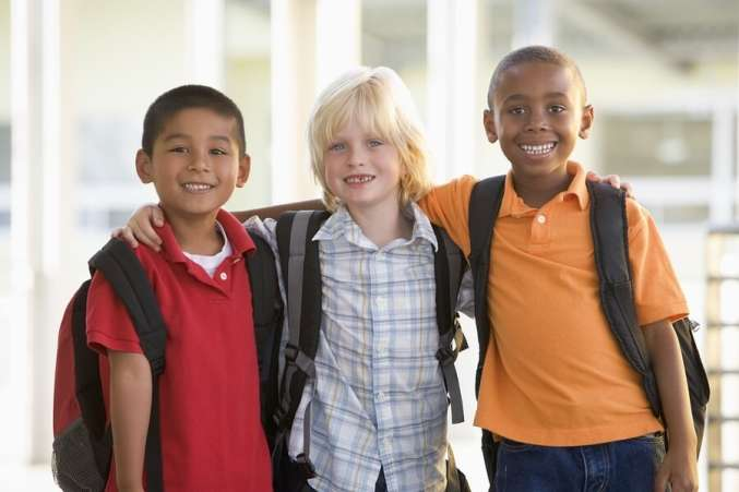 Three boys with backpacks smiling