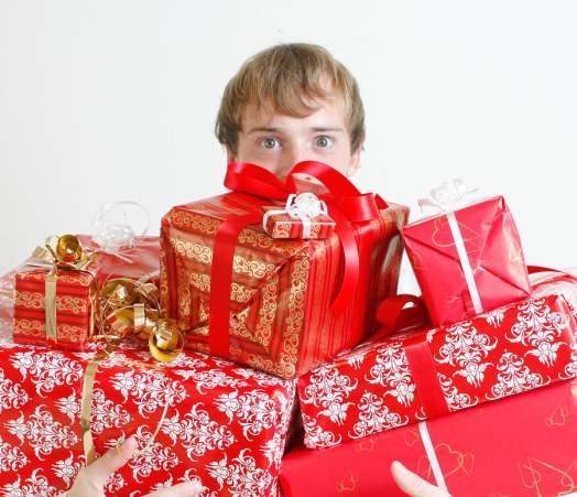 man peeking over tall stack of presents