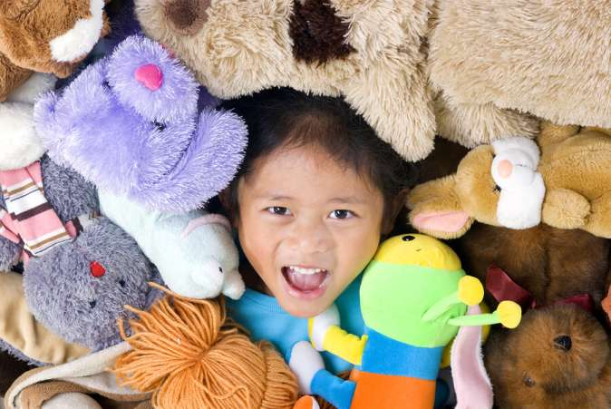 Child surrounded in toys