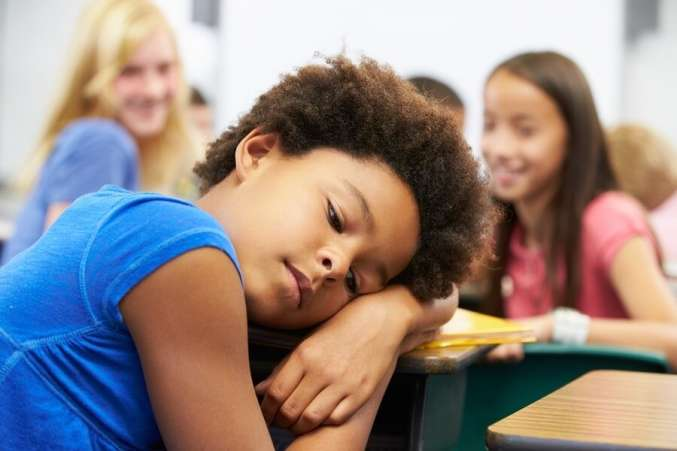 Unhappy girl being bullied in classroom