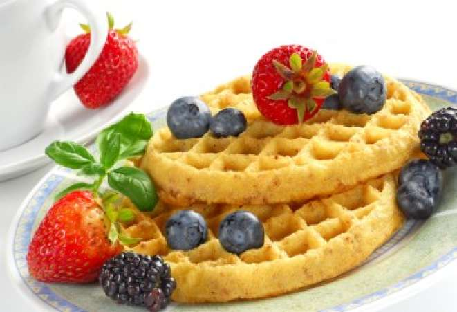 Plate of waffles and berries on table.