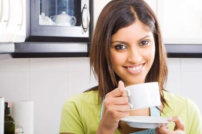 Smiling woman drinking coffee in kitchen