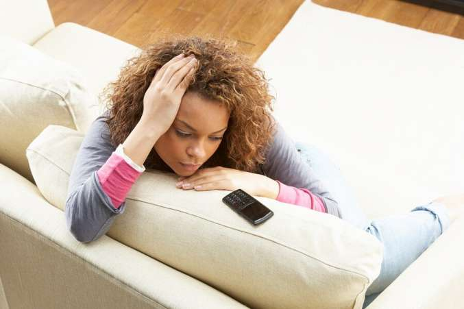 Sad woman sitting on couch looking at phone