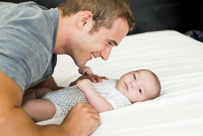Young Dad Smiling with New Baby