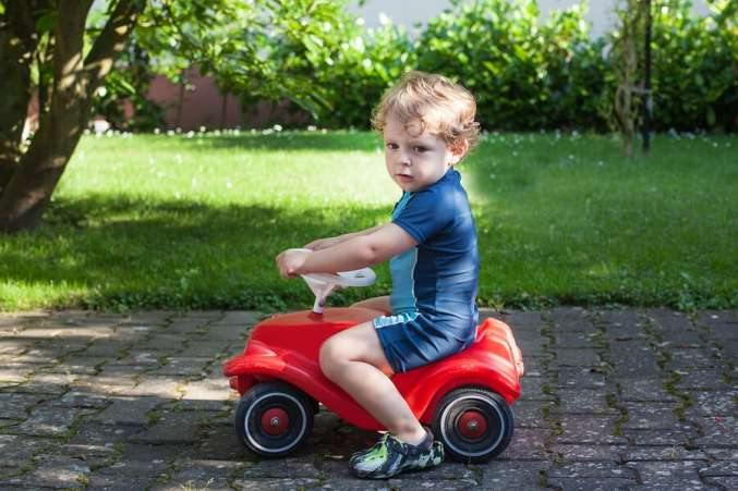 boy riding in toy car