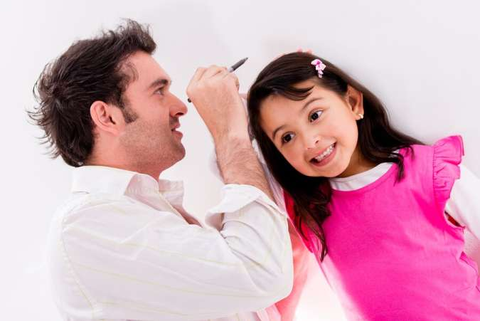 father measuring daughter