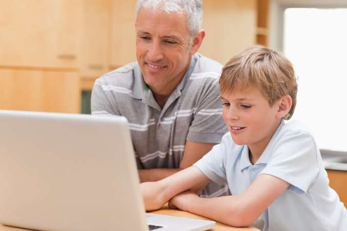 Homework help, father and son using computer