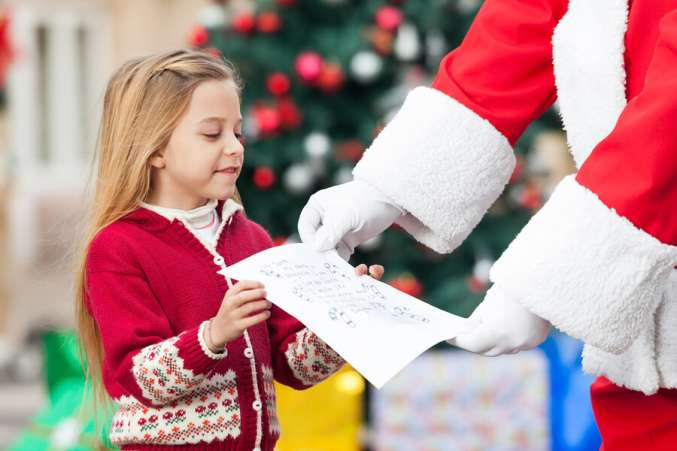 child giving letter to Santa