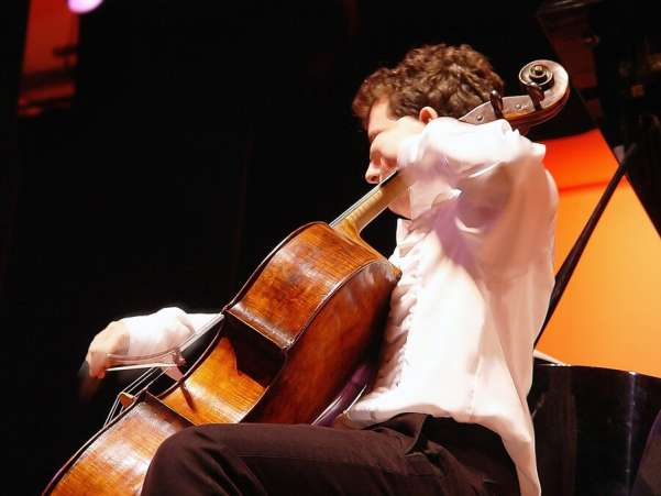 what colleges look for, boy playing cello instrument