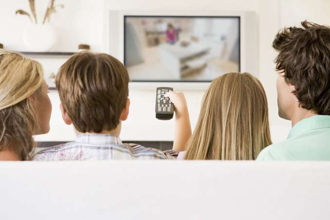 Back shot of family watching television together
