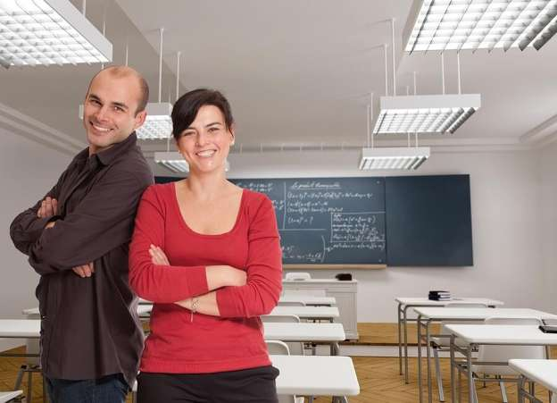 Parent and teacher sitting together in classroom
