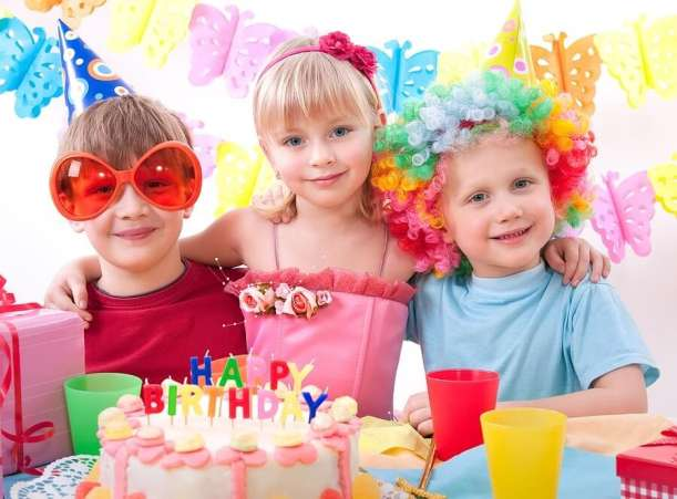Three kids at birthday party in front of cake