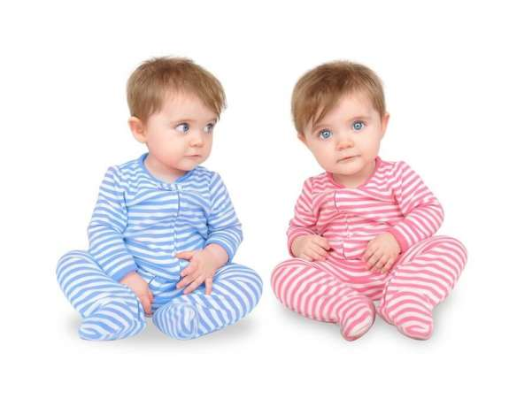 Twins in striped pink and blue pajamas against white background