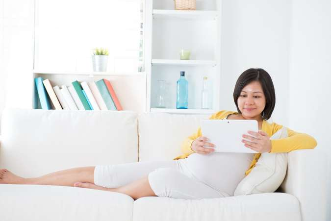 Pregnant woman reading tablet on couch