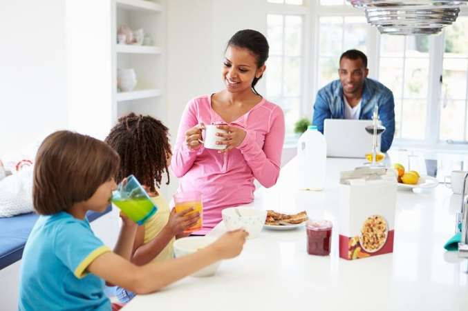 Family routine eating breakfast in kitchen