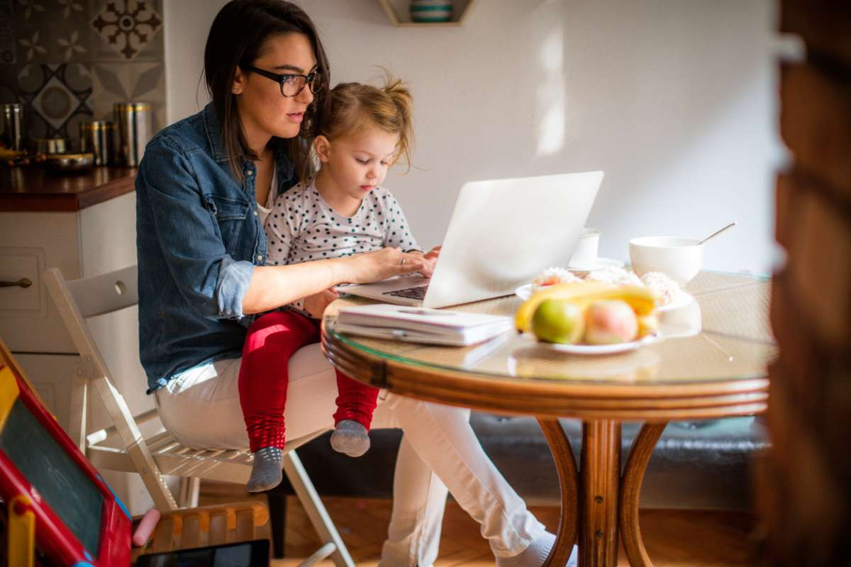 mom working on side hustle at home with toddler
