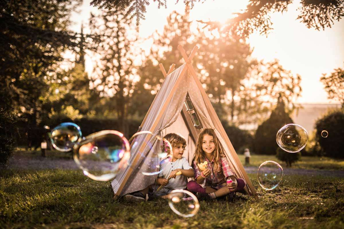 kids playing with toys in tent in summer