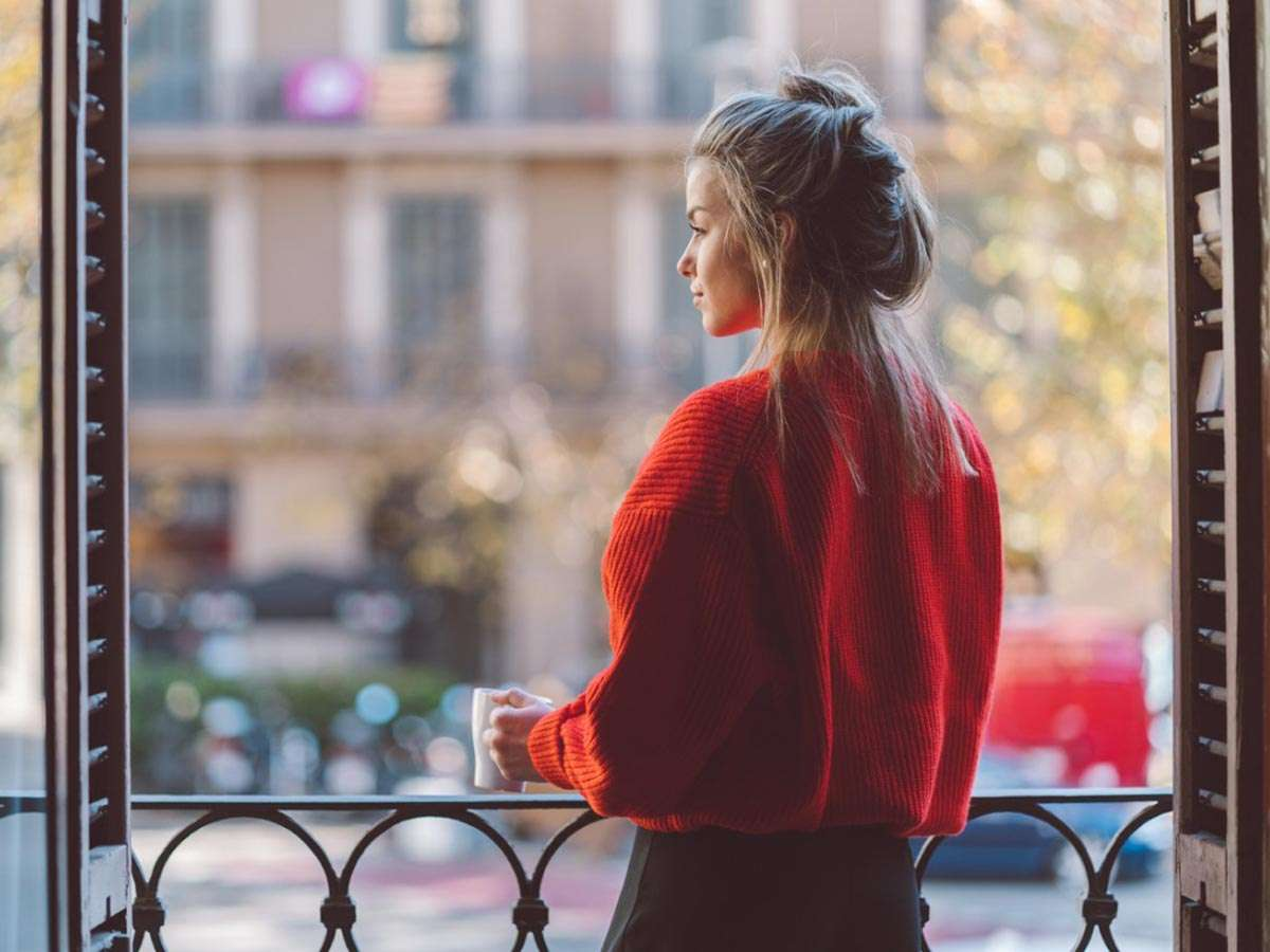 woman practicing mindfulness drinking coffee on balcony