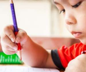 Preschool boy holding red pencil