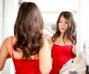 Teen girl trying on red dress
