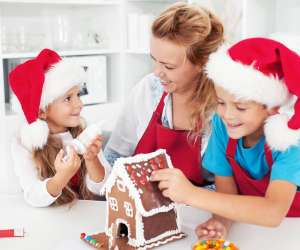 traditional christmas activity, mom and kids make gingerbread house