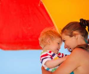 Mom and baby sitting under umbrella at the beach