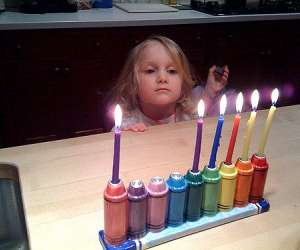 girl lighting menorah