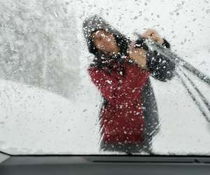 Teen Cleaning Off Icy Windshield Wiper