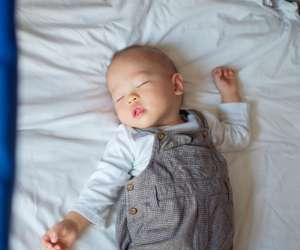 baby sleeping in crib next to parents bed