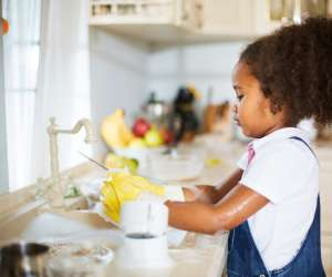 little girl learning chores and washing dishes