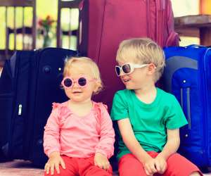 kids with fully packed suitcases ready for family vacation