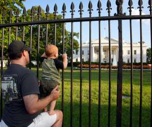 dad and baby peering into fence of the white house