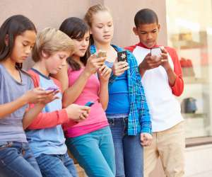 group of kids with smartphones vs. flip phones